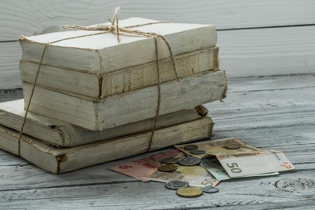 Velhos livros brancos com dinheiro e moedas na parede de madeira