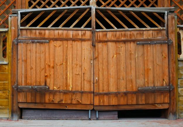Velhos portões de madeira trancados com viga de madeira