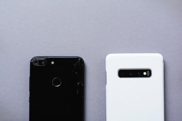 Velhos smartphones pretos e novos brancos quebrados em fundo cinza. o conceito de reciclagem de telefones e tecnologias. vista do topo.