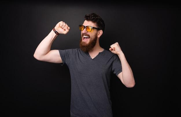 Vencedor com barba comemorando com as mãos levantadas em pé sobre o fundo escuro e isolado