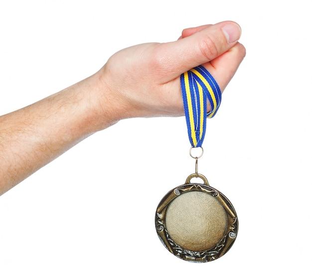 Vencedor da medalha de ouro na mão. em uma parede branca.
