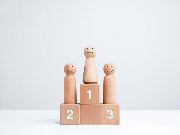 Vencedor do concurso de negócios. mulher sorridente em pé no pódio do vencedor no primeiro prêmio, figura de madeira no bloco de cubos de madeira em fundo branco. poder, objetivos, sucesso e conceito de liderança das mulheres.