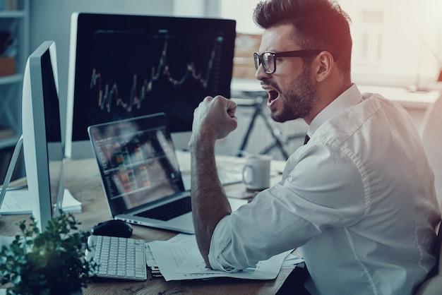 Vencedor do negócio. jovem empresário em trajes formais gesticulando enquanto usa o computador no escritório