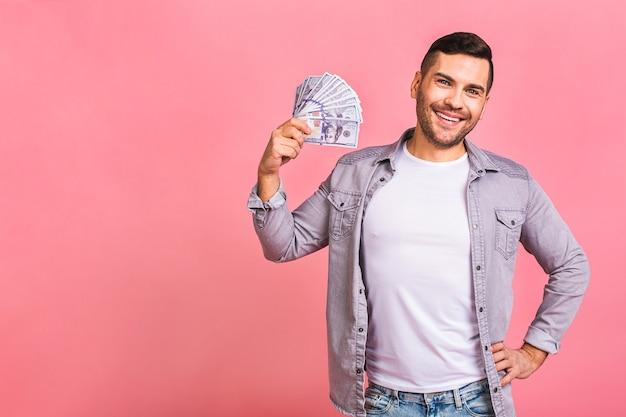 Vencedor feliz jovem rico casual segurando dinheiro notas de dólar com surpresa isolada sobre rosa.