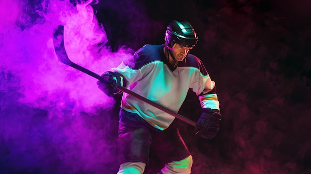 Vencedora. jogador de hóquei masculino com o taco na quadra de gelo e a parede de néon escuro. desportista com equipamento, treino de capacete. conceito de esporte, estilo de vida saudável, movimento, bem-estar, ação.