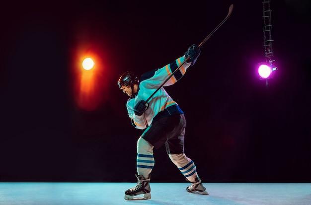 Vencedora. jogador de hóquei masculino com o taco na quadra de gelo e fundo colorido de néon escuro. desportista com equipamento, treino de capacete. conceito de esporte, estilo de vida saudável, movimento, bem-estar, ação.