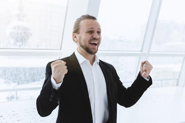 Vencendo o homem feliz sucesso em pé ao lado da janela e rindo com as mãos. vitória