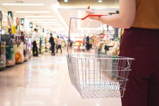 Venda, compras, consumismo e conceito de pessoas - mulher com cesta de alimentos no supermercado