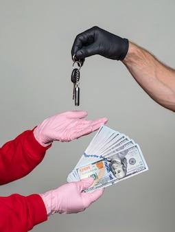 Venda de carros durante a pandemia de covid-19. mão feminina segurando dólares, homem segurando as chaves do carro
