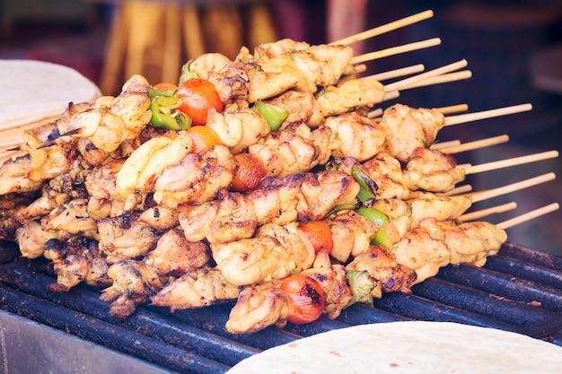 Venda de espetos de kebab preparados com carvão