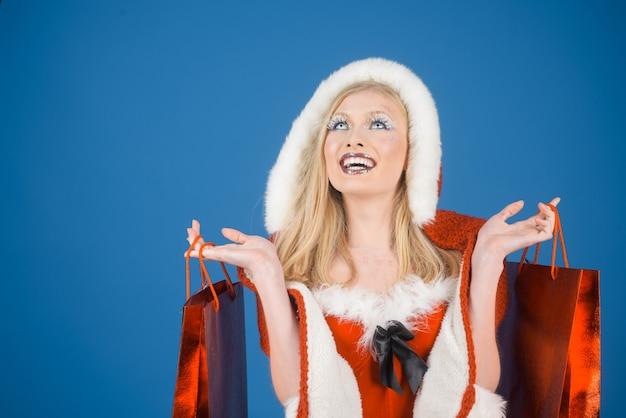 Venda de natal, compras, feriados de ano novo e conceito de pessoas, mulher bonita sorridente no papai noel