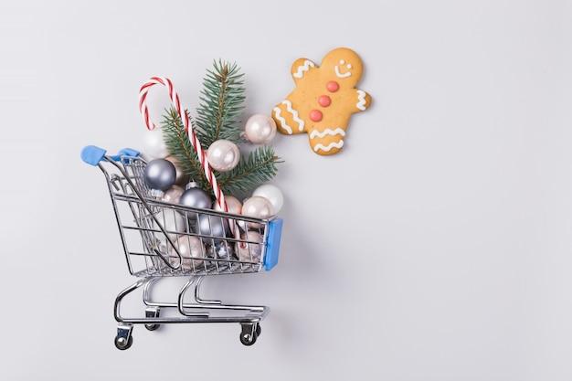 Venda de natal, conceito de compras - carrinho de carrinho cheio de bolas e árvore de natal. vista do topo. copyspace.