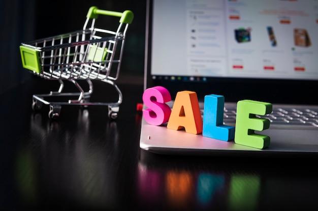 Venda de palavras de madeira multicolorida definida na parte inferior do laptop no fundo da página da web aberta na tela e o pequeno carrinho de compras. conceito de compras online. boa compra na internet. venda em e-commerce.