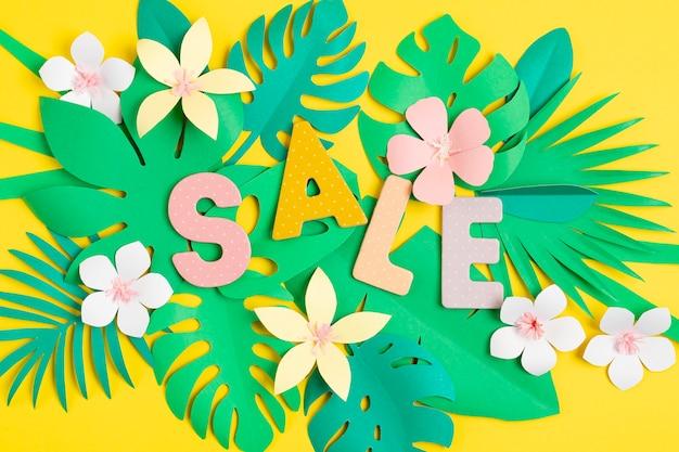 Venda de palavras sobre fundo de folhas de corte de papel tropical