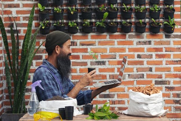 Venda de plantas online; homem segurando um vaso de plantas e um laptop
