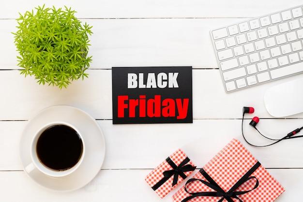 Venda de sexta-feira negra com xícara de café, mesa de planta, caixa de presente em fundo branco de madeira