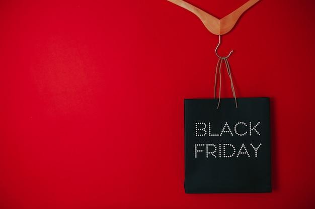 Venda de sexta-feira negra plana leigos, saco de sexta-feira negra, cabides na superfície vermelha,