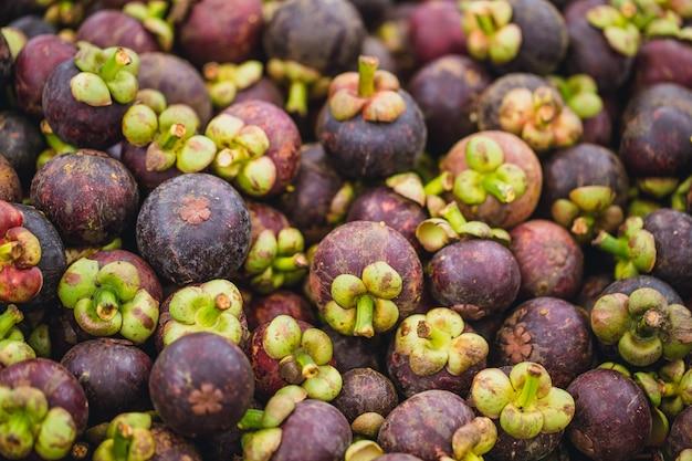 Venda do fruto tropical do mangustão no mercado de rua no asiático de tailândia.