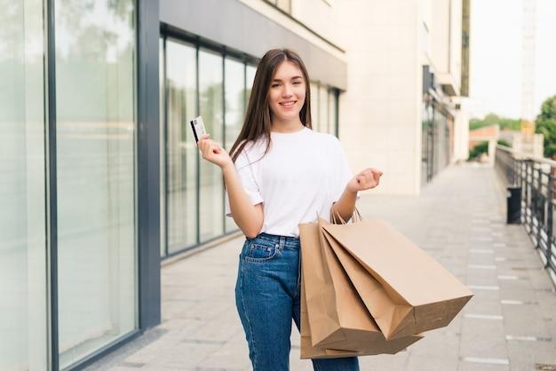 Venda e turismo, conceito de pessoas felizes - linda mulher segurando um cartão de crédito com sacolas de compras na cidade