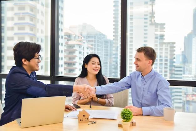 Venda homem apertar mão cliente casal acordo negócio comprar casa