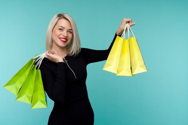 Venda. jovem mulher sorridente segurando sacolas de compras em preto feriado de sexta-feira. garota feliz no espaço azul