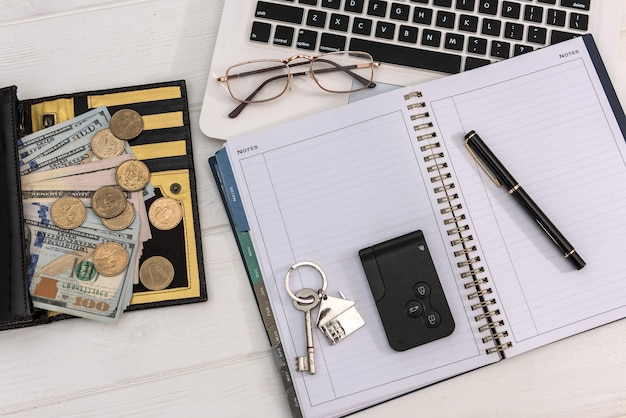 Venda ou aluguel, carro e chaves de casa com contas de dólar no teclado do laptop, conceito de economia