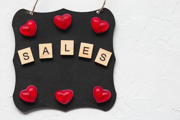 Venda palavra e corações no quadro negro como conceito de compras para o dia dos namorados
