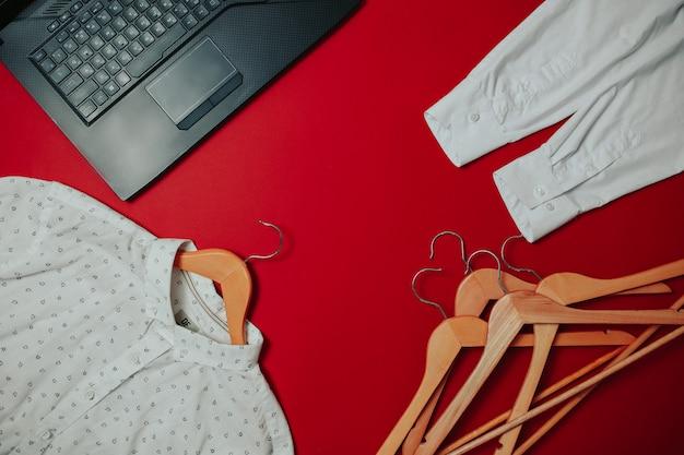 Venda plana de sexta-feira preta, sacola de sexta-feira preta, cabides e camisa na superfície vermelha, caderno preto e touchpad,