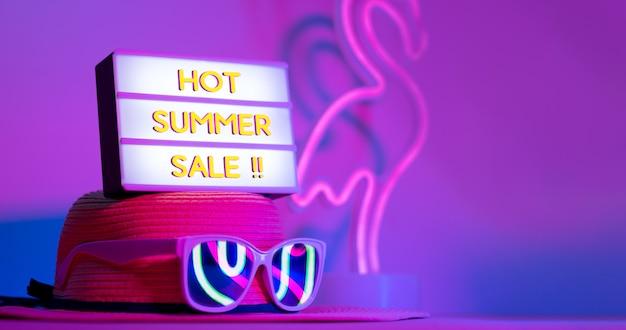 Venda quente de verão em caixa de luz no chapéu com óculos de sol neon rosa e azul e verde luz na mesa