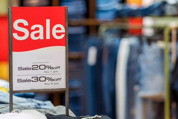 Venda simulado anunciar configuração do quadro de exibição sobre a pilha de jeans e linha de roupas