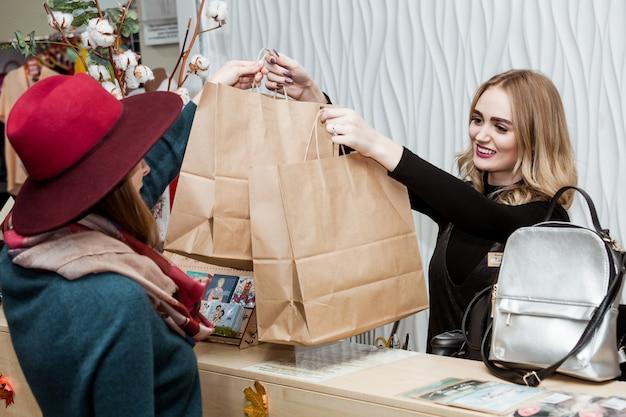 Venda sorridente jovem mulher sacos de compras