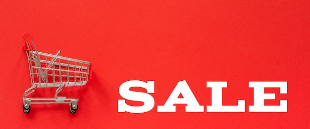 Venda vazia pequena do carro e do texto do trole da compra no fundo vermelho.