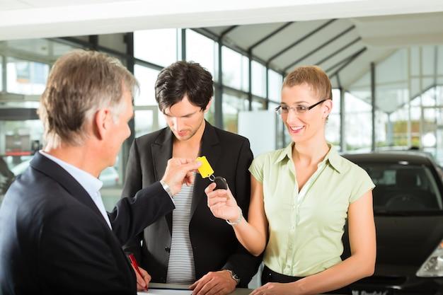 Vendas de carros - revendedor entregando chave de automóvel mulher