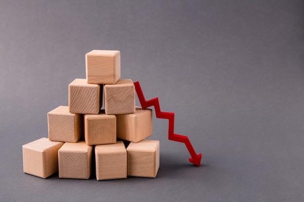Vendas de cubos de madeira em pirâmide de pilha caindo seta apontando