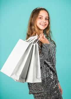 Vendas e descontos. menina pequena com sacolas de compras. criança feliz. menina com presentes. conceito de consumismo. moda rápida. prepare-se para a festa. centro de compras. economia na compra de férias. compras para casa.