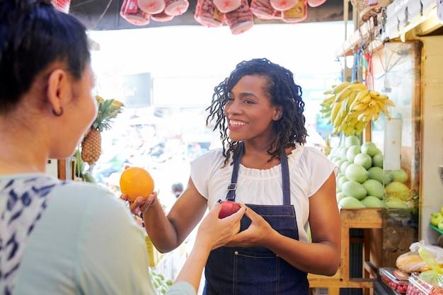 Vendedor ajudando o cliente no mercado local