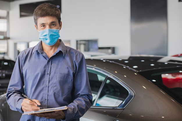 Vendedor asiático usa máscara cirúrgica trabalhando como inspetor, verificando a escrita na prancheta na garagem da concessionária