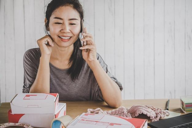 Vendedor asiático vendendo on-line falando no telefone inteligente