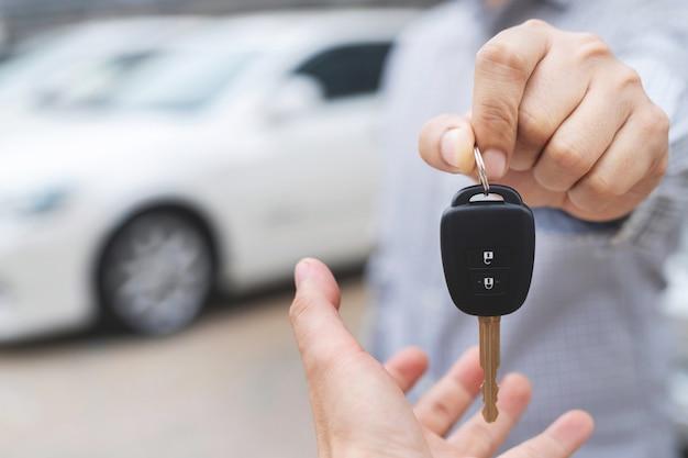 Vendedor com a chave de um carro na mão