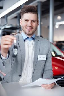 Vendedor com as chaves do carro na frente da câmera