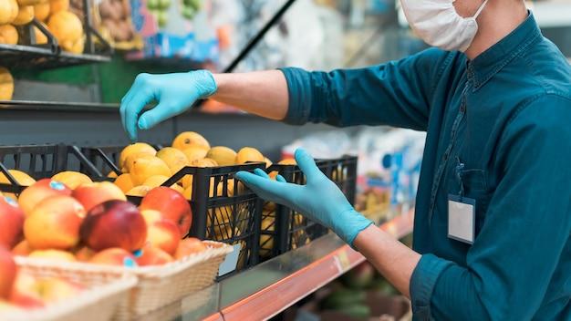 Vendedor com uma máscara protetora em frente ao balcão com frutas