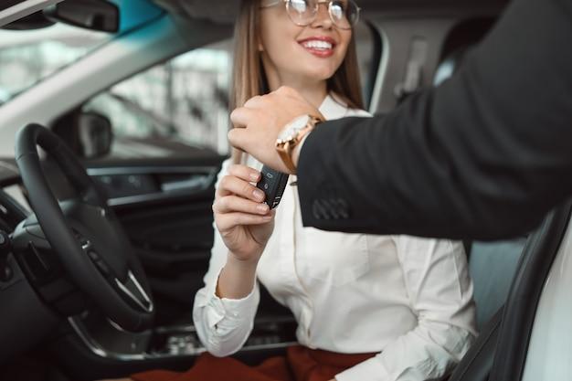 Vendedor dando a chave do carro novo para uma jovem