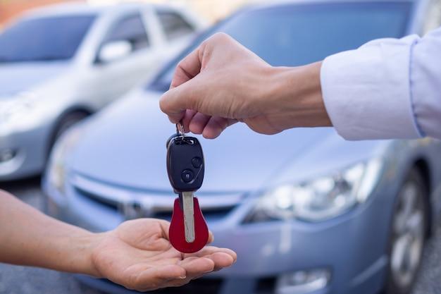Vendedor dando carro chave para um comprador