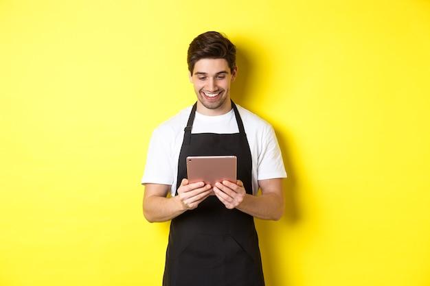 Vendedor de avental preto olhando para a tela do tablet digital, sorrindo satisfeito, de pé sobre a parede amarela