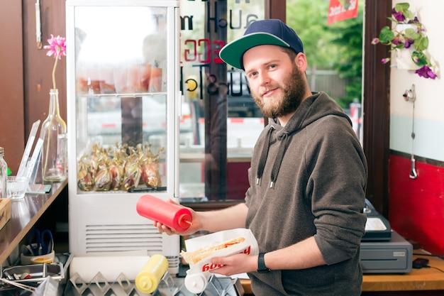 Vendedor de cachorro-quente e ingredientes frescos em uma lanchonete fast food