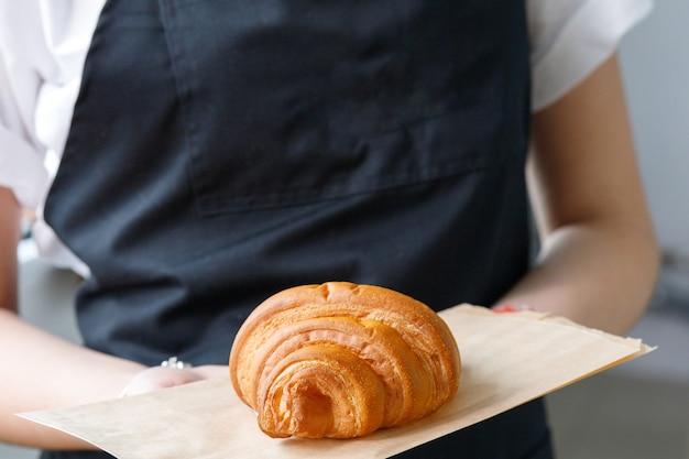 Vendedor de café segurando um croissant em uma bandeja