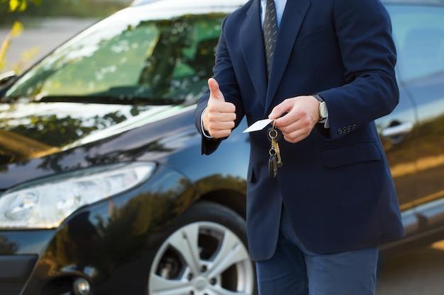 Vendedor de carro clássico jovem bonito parado na concessionária segurando uma chave