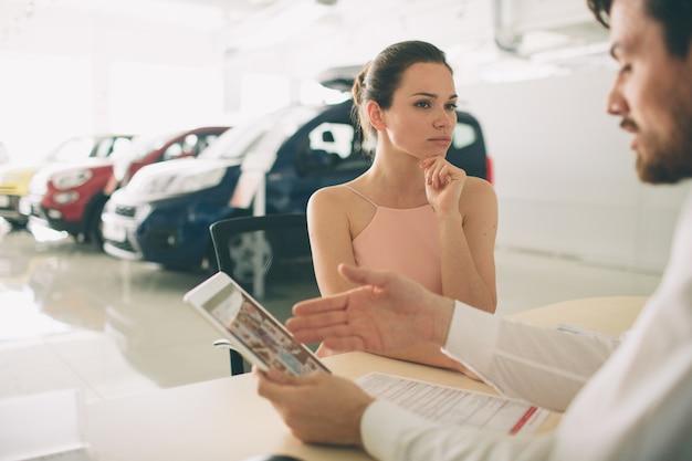 Vendedor de carros amigável conversando com uma jovem mulher e mostrando um carro novo dentro da sala de exposições assinatura do contrato.