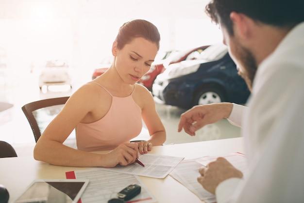 Vendedor de carros amigável conversando com uma jovem mulher e mostrando um carro novo dentro da sala de exposições