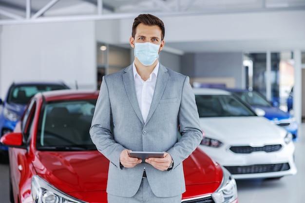 Vendedor de carros com máscara facial em pé no salão de automóveis e segurando o tablet enquanto olha para a câmera. novo normal.